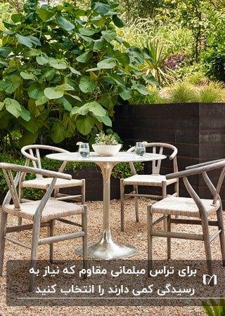میز گرد و چهار صندلی چوبی در تراسی با کفپوش سنگ ریزه