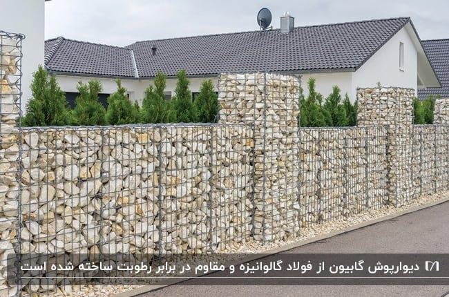 دیوارپوش گابیون رنگ روشن برای حیاط خانه ای پر از درختچه های کوچک