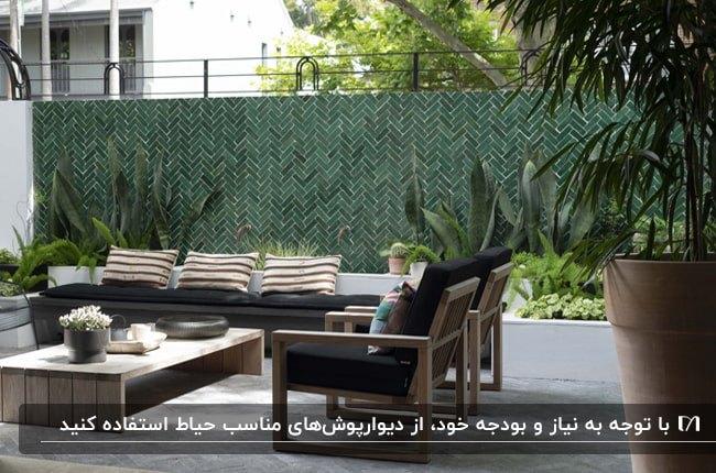 حیاطی با مبلمان چوبی و پارچه مشکی به همراه کوسن های رنگی و دیوارپوش کاشی های سبز رنگ