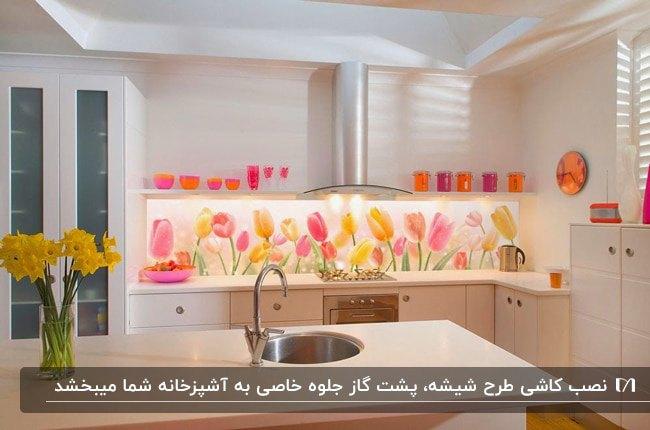 آشپزخانه ای با کابینت های سفید، جزیره سفید و کاشی بین کابینتی طرح شیشه با گلهای زرد و صورتی