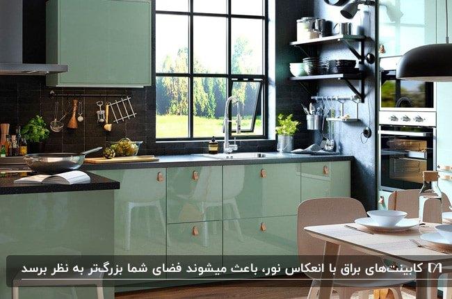 آشپزخانه کوچکی با دیوار مشکی و کابینت های براق سبز روشن