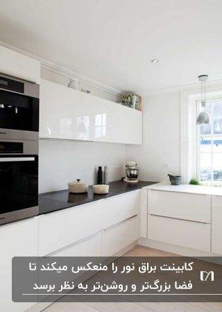 آشپزخانه ای با کابینت های براق سفید و رویه مکشی