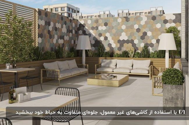 دیوارپوش کاشی های شش ضلعی به رنگ طوسی، قهوه ای، طلایی و کرم در حیاطی با مبلمان راحتی کرم و فریم چوبی