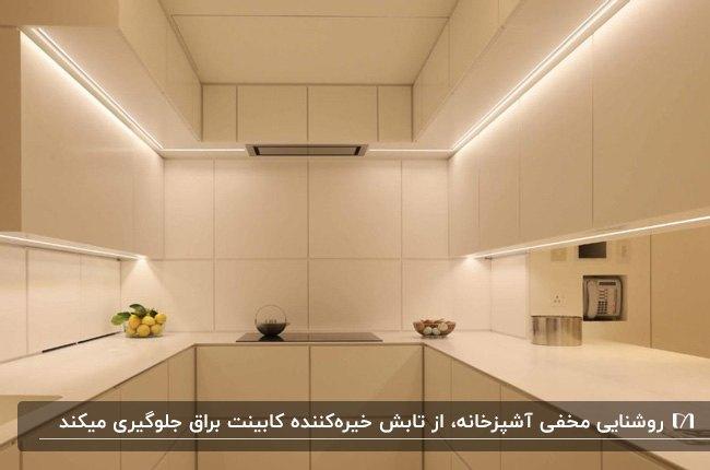 آشپزخانه ای با کابینت یو شکل سفید و کاشی های بین کابینتی سفید به همراه نورپردازی مخفی کابینت