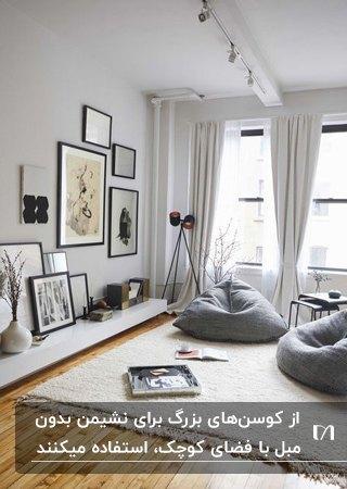 نشیمن بدون مبل با فرش طوسی روشن، دو مبل بالین و قاب عکس هایی روی دیوار