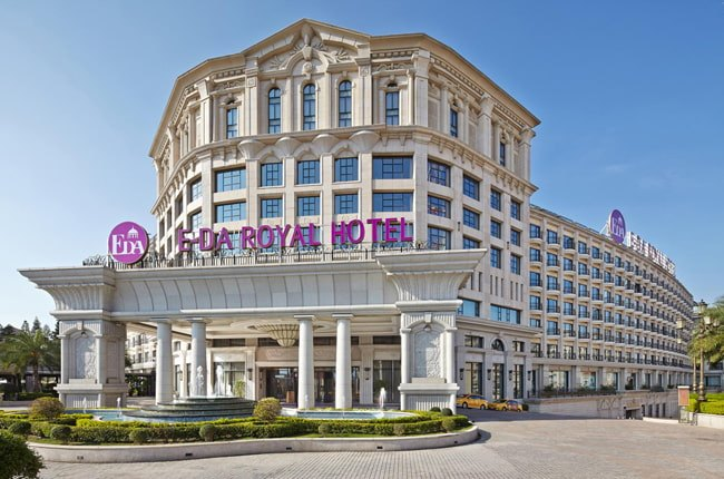 تصویری از نمای خارجی ساختمان سفید رنگ هتلی بزرگ با آبنما و میدانی اختصاصی در ورودی هتل