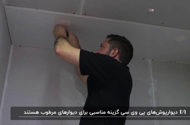 تصویر مردی در حال نصب دیوارپوش طوسی پی وی سی