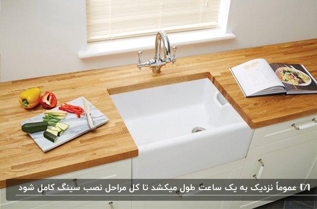 آشپزخانه ای با سینک مربع شکل سفید، کابینت سفید و صفحه رویی چوبی