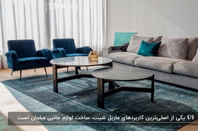 نشیمنی با مبلمان کرم و آبی، فرش آبی و دو میز جلو مبلی گرد مرمر مشکی