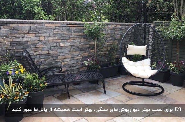 دیوارپوش سنگی با رنگ های تیره برای دیوار حیاط با صندلی تابی پایه دار آویز و صندلی راحتی استخری مشکی