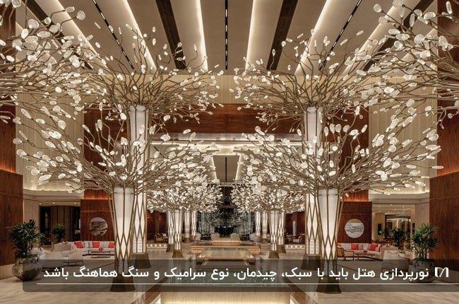 طراحی داخلی لابی هتلی با تم رنگی کرم و زرشکی و نورپردازی با لامپ های تزیینی