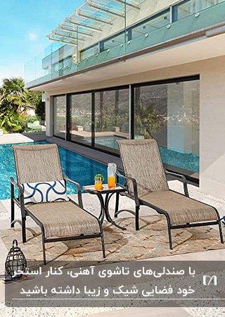 دو صندلی تاشو آهنی با تکیه گاه قابل تنظیم با فریم مشکی کنار استخر در حیاط ویلا
