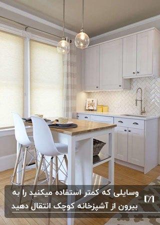 آشپزخانه ای کوچک و کم جا با کابینت های سفید، کانتر سفید با رویه چوبی و صندلی های سفید