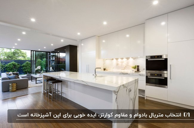 آشپزخانه بزرگی با کابینت های سفید براق ، کانتر سنگی سفید با رگه های طوسی و چهارپایه های مشکی