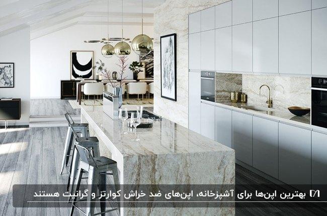 آشپزخانه ای با کابینت های بالا و پایین سفید براق، اپن سنگی رگه دار و چهارپایه های نقره ای