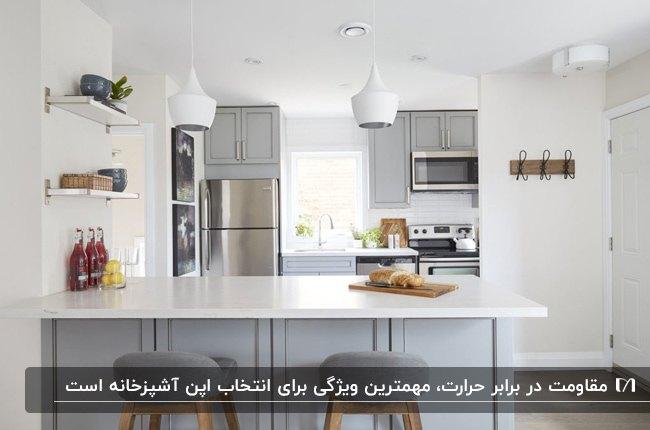 آشپزخانه ای با لوازم برقی سیلور، کابینت ها و اپن طوسی با صفحه رویی اپن سفید