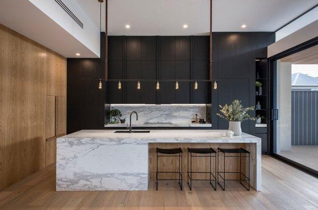 آشپزخانه ای با کابینت های زغالی، کانتر سنگی سفید با رگه های طوسی با دیوارپوش و کفپوش چوبی