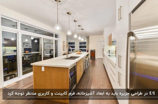 آشپزخانه ای با کابینت های یک طرفه سفید و جزیره چوبی به همراه لوستر های آویز بالای جزیره