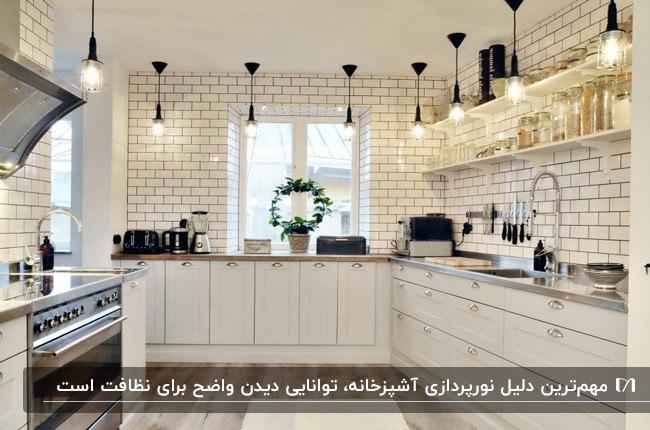 آشپزخانه ای با کابینت های و کاشی های بین کابینتی سفید به همراه روشنایی های آویز مشکی