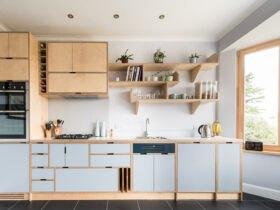 آشپزخانه ای با کابینت های یک طرفه و ویترین های طبقه ای بدون درب به رنگ چوب و آبی