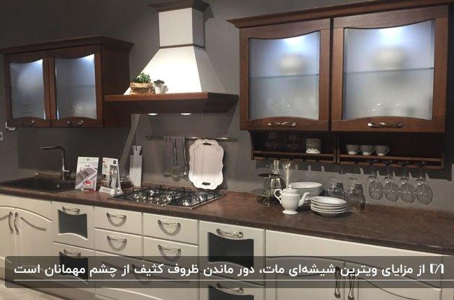 آشپزخانه ای با کابینت های کرم و قهوه ای و ویترین هایی با درب شیشه ای مات