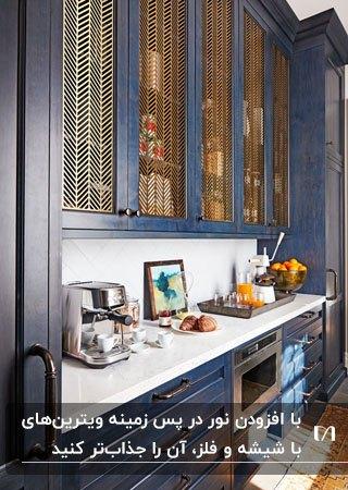 آشپزخانه ای با کابینت های سرمه ای، صفحه رویی کابینت سفید و ویترین هایی با درب شیشه ای و فلزی