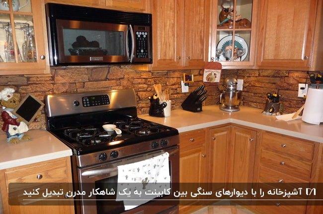 آشپزخانه ای با کابینت های چوبی عسلی رنگ، دیوارپوش بین کابینتی سنگی هم رنگ کابینت و گاز مشکی و نقره ای