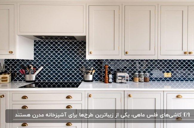 آشپزخانه ای با کابینت های سفید و کاشی بین کابینتی سرمه ای با طرح فلس ماهی
