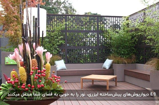 حیاطی با دیوارپوش لیزری فلزی مشکی، نیمکت های قهوه ای و گلدان گل