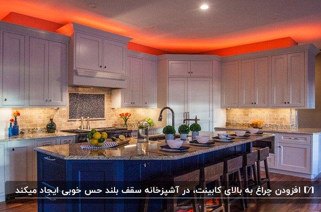 آشپزخانه ای با کابینت های قهوه ای، جزیره آبی ، چهارپایه های چوبی قهوه ای و نورپردازی نارنجی بالای کابینت