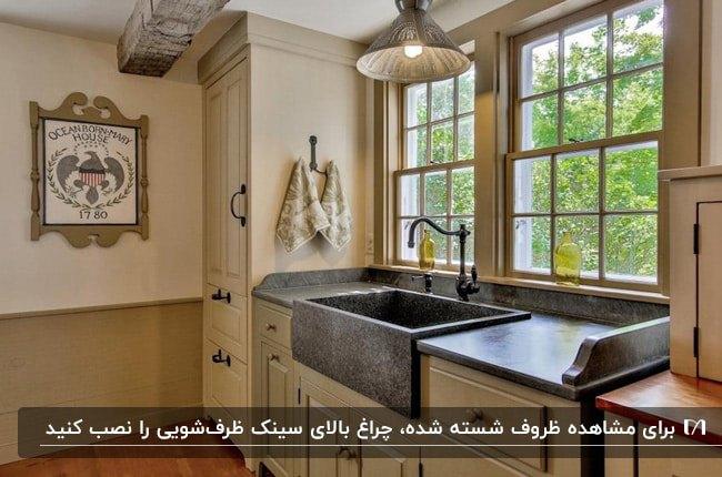آشپزخانه ای با کابینت های نخودی رنگ، سینک سنگی خاکستری و چراغ آویز برای روشنایی بالای سینک