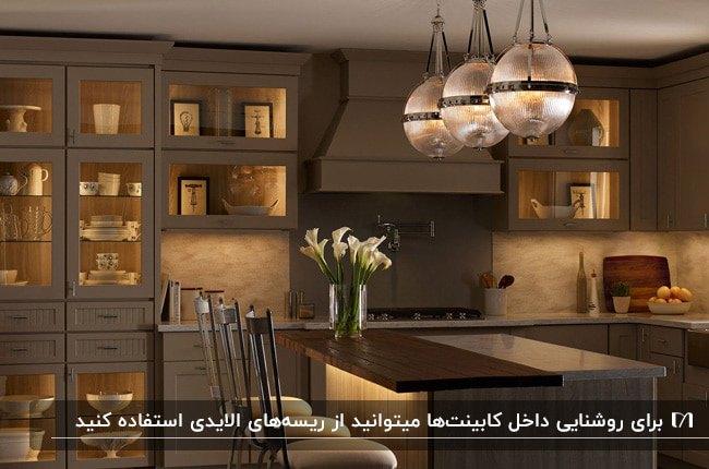 آشپزخانه ای با تم رنگی کرم و قهوه ای، سه لوستر گرد آویز و نورپردازی داخل کابینت های با در شیشه ای