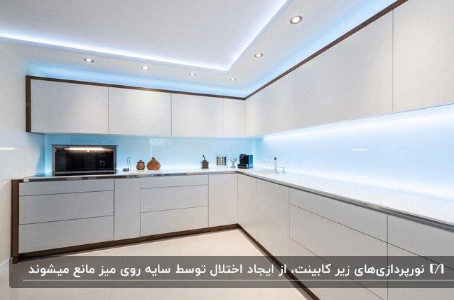 آشپزخانه ای با کابینت ال شکل سفید و نورپردازی سفید و آبی زیر کابینت