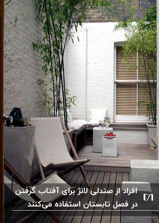 تراسی با دیوارهای سفید و صندلی های لانژ چوبی با پارچه سفید