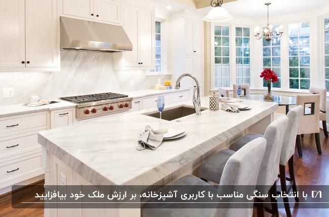 آشپزخانه ای با کابینت های سفید ، هود و اجاق گاز نقره ای و سنگ اپن مرمر