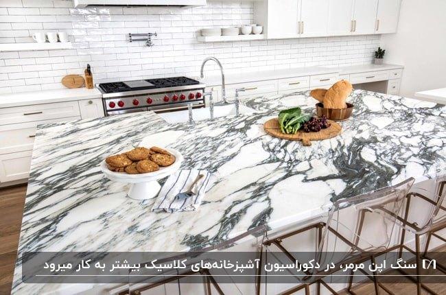 آشپزخانه ای با کابینت سفید، کاشی بین کابینتی سفید و سنگ اپن مرمر سفید و طوسی
