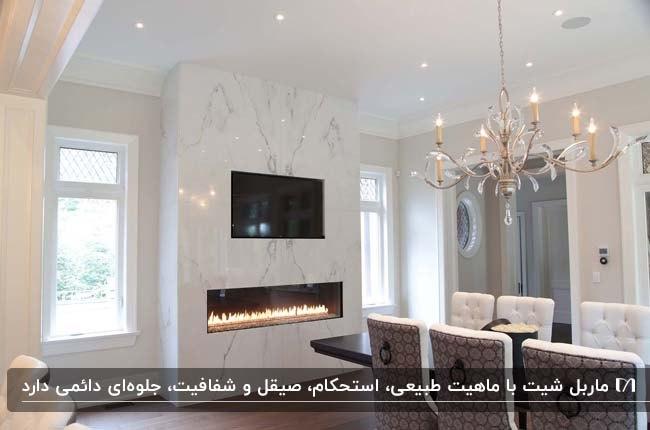 سالنی با میز غذاخوری چوبی و تلویزیون روی دیوار ماربل شیت سفید