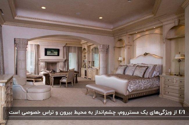 تصویر یک مستر روم طلایی و صورتی کمرنگ با شومینه، تخت دو نفره، پاف تخت و مبلمان راحتی