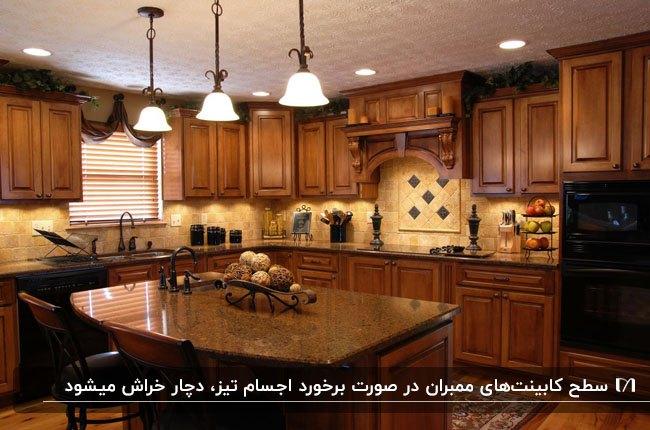 تصویر آشپزخانه ای سنتی با کابینت ممبران قهوه ای و سه لوستر آویز بالای جزیره