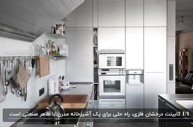 آشپزخانه ای به سبک صنعتی با کابینت های فلزی نقره ای و تخته چوبی کنار سینک