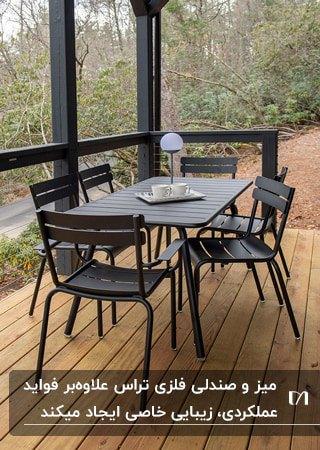 میز مستطیلی و صندلی های فلزی مشکی روی تراسی با حفاط مشکی