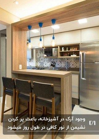 آشپزخانه ای با کابینت های کرم رنگ و آرک مستطیلی چوبی با چراغ های آویز آبی