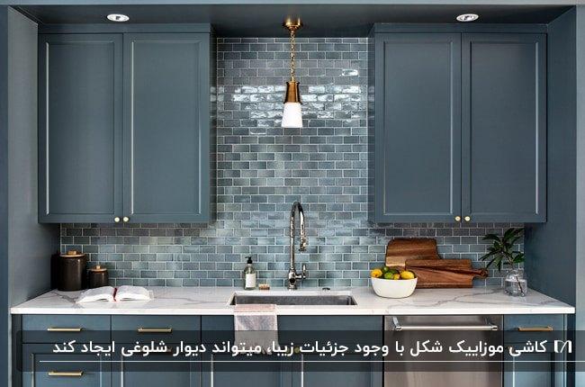 آشپزخانه ای با کابینت های آبی تیره و کاشی طرح موزاییک آبی براق