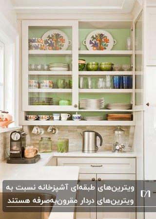 تصویری از بخش ویترین های طبقه ای سبز و سفید در آشپزخانه ای با کابینت های سفید