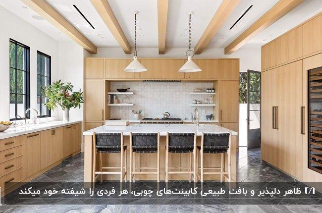 آشپزخانه ای مدرن با کابینت هایی از چوب طبیعی، چهارپایه های چوبی و مشکی با لوستر آویز