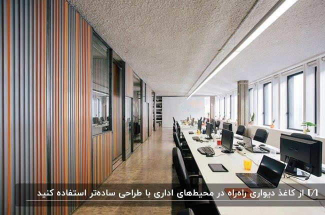 اداره ای با میز سفید و صندلی های مشکی به همراه کاغذدیواری راه راه رنگی