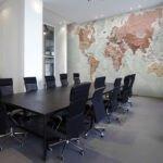 اتاق کار اداره ای با میز جلسه قهوه ای و صندلی های مشکی چرخدار با کاغذدیواری طرح دار طرح نقشه