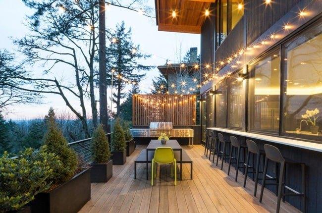 تراسی با کفپوش چوبی و فلاورباکس هایی با درختچه های کاج و ریسه های نوری روی سقف