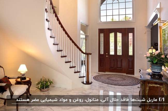 راهروی ورودی خانه ای با پله مارپیچ، حفاظ پله و درب چوبی به همراه کفپوش ماربل شیت سفید