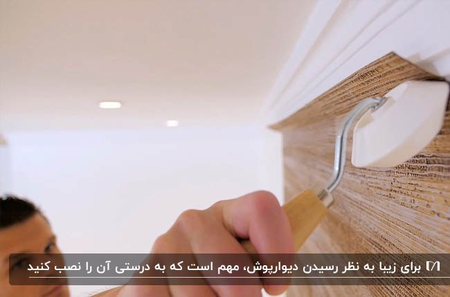 تصویر دیوارپوش طرح چوب در حال نصب توسط یک مرد